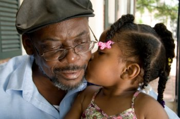 Little girl kissing grandfather.