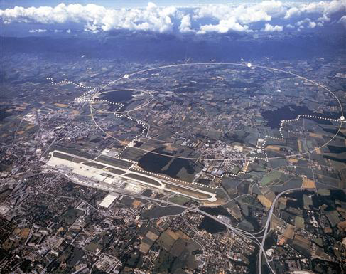 Aerial view of the CERN site just outside Geneva. The underground particle accelerators (with circumferences of 27 km and 7 km) allow scientists to look at tiny scales. Image © <a href='http://public.web.cern.ch/Public/Welcome.html'>CERN</a>.